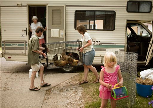 The Morrison family, Dee, top left, Taylor, 4, right, Bob, and Jeni, center, pack up their belongings following a mandatory evacuation ordered for Los Alamos, N.M., as the rapidly-growing Las Conchas wildfire approaches, Monday, June 27, 2011. The blaze, which began Sunday, has destroyed 30 structures south of Los Alamos and forced the closure of the Los Alamos Nuclear Laboratory. &#40;AP Photo&#47;Craig Fritz&#41; <span class=meta>(AP Photo&#47; Craig Fritz)</span>