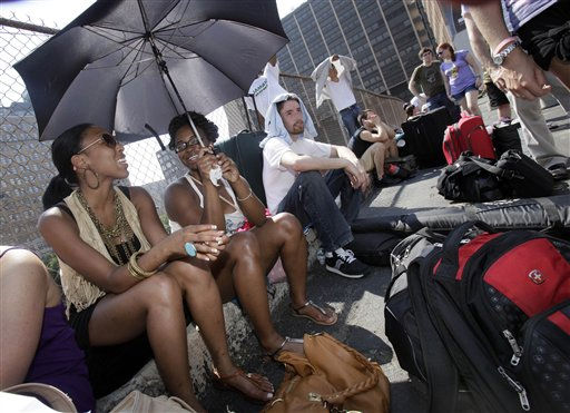 Breayana Bennett, left, and Patrice Walton share an umbrella to shade themselves from the sun as they wait with others in a New York parking lot on Friday, July 22, 2011 for a Megabus to Albany, N.Y. Temperatures in New York reached over 100 degrees Fahrenheit. &#40;AP Photo&#41; <span class=meta>(AP Photo&#47; Anonymous)</span>