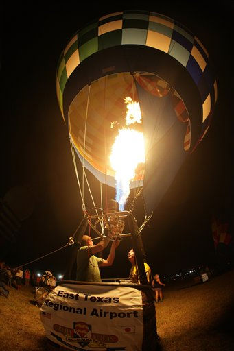Pilot Paul Petrehn, from Ann Arbor, Mi, and a member of his crew fire his balloon&#39;s envelope during the balloon glow as part of the opening ceremonies of the 33nd annual &#34;Great Texas Balloon Race&#34; in Longview, Texas on Friday night, July 29, 2011.   &#40;AP Photo&#47;Scott M. Lieberman&#41; <span class=meta>(AP Photo&#47; Scott M. Lieberman)</span>