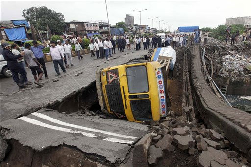 People stand around an area where a truck fell after a bridge caved in, in Mumbai, India, Saturday, Aug. 6, 2011.There were no casualties reported in the incident. &#40;AP Photo&#47;Rajanish Kakade&#41; <span class=meta>(AP Photo&#47; Rajanish Kakade)</span>