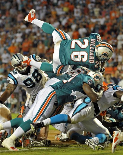 Miami Dolphins running back Lex Hilliard &#40;26&#41; leaps over the line for a touchdown during the first half of an NFL preseason football game against the Carolina Panthers, Friday, Aug. 19, 2011, in Miami. &#40;AP Photo&#47;Gary I. Rothstein&#41; <span class=meta>(AP Photo&#47; Gary I. Rothstein)</span>