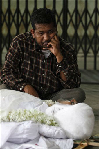 A relative sits by the body of Amitabh Das, 33, a victim of a fire, at an electric crematorium in Kolkata, India, Saturday, Dec. 10, 2011.  The private Indian hospital where dozens of people died in a massive fire had failed to update its safety procedures despite being ordered to do so months ago, officials said Saturday. Most of the victims died in their beds from inhaling noxious black smoke that filled the rooms and corridors of one of AMRI Hospital&#39;s three buildings after the fire broke out before dawn Friday in the basement and medical staff fled the scene. &#40;AP Photo&#47;Anupam Nath&#41; <span class=meta>(AP Photo&#47; Anupam Nath)</span>