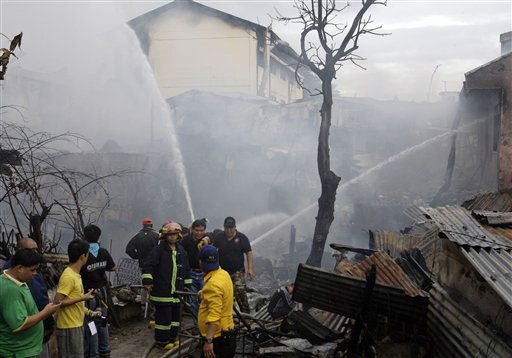 Firefighters gather around the remains of houses that caught fire after a plane crashed into a nearby school Saturday, Dec. 10, 2011 in suburban Paranaque City, south of Manila, Philippines. The light plane crashed into the school building Saturday near the Philippine capital after its pilot requested an emergency landing shortly after takeoff, killing over a dozen of people. &#40;AP Photo&#47;Pat Roque&#41; <span class=meta>(AP Photo&#47; Pat Roque)</span>