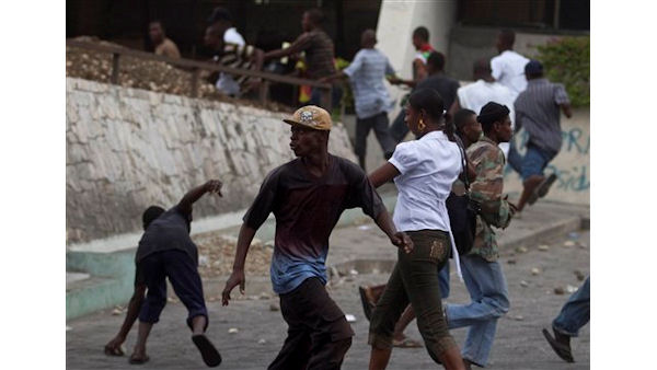 "<div class=""meta ""><span class=""caption-text "">Protesters run away from U.N. peacekeepers during a protest  as a woman walks by in Port-au-Prince, Haiti, Friday, Dec. 10, 2010. Despite the country's electoral council announcement Thursday of a compromise to recount votes, clashes between protesters and authorities continued in Port-au-Prince. (AP Photo/Guillermo Arias) (AP Photo/ Guillermo Arias)</span></div>"