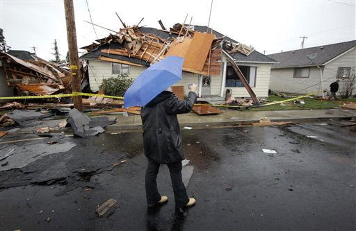 A unidentified woman uses her cell to take pictures of a damaged home after a tornado that touched down on Tuesday, Dec. 14, 2010, in Aumsville, Ore. The tornado struck the small town on Tuesday, tearing roofs off buildings, hurling objects into vehicles and homes and uprooting trees. No injuries were reported. There were early reports that some people had been trapped in cars..&#40;AP Photo&#47;Rick Bowmer&#41; <span class=meta>(AP Photo&#47; Rick Bowmer)</span>