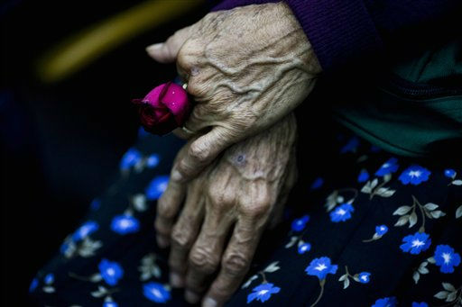 Cristina Alfaro Mejia, whose husband and daughter were killed by soldiers during a massacre in the community of  Dos Erres  in 1982,  holds a rose while waiting to the sentence in Guatemala City, Tuesday, Aug. 2, 2011.  The court sentenced three former special forces soldiers to 6,060 years in prison each for the massacre of more than 200 men, women and children, one of hundreds that occurred during Guatemala&#39;s 36-year civil war, which ended in 1996. Some 240,000 people, mostly Mayan Indians, vanished or died.&#40;AP Photo&#47;Rodrigo Abd&#41; <span class=meta>(AP Photo&#47; Rodrigo Abd)</span>