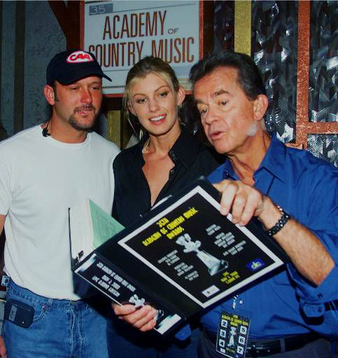 Dick Clark, right, producer of the 35th Annual Academy of Country Music Awards, looks over the show&#39;s script with Tim McGraw and Faith Hill, the husband-wife team both nominated for several awards including each for Entertainer of the Year, during rehearsals Tuesday, May 2, 2000, at the Universal Amphitheatre in Universal City, Calif. The awards are to be presented Wednesday, May 3 on CBS. &#40;AP Photo&#47;Reed Saxon&#41; <span class=meta>(AP Photo&#47; REED SAXON)</span>