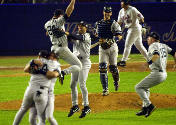 New York Yankees first baseman Tino Martinez &#40;24&#41; jumps into the arms of pitcher Mariano Rivera as catcher Jorge Posada, third from right, Scott Brosius &#40;18&#41; and others celebrate after defeating the New York Mets in Game 5 of the World Series 4-2 to become the 2000 World Series Champions Thursday, Oct. 26, 2000, at New York&#39;s Shea Stadium. Mets&#39; Benny Agbayani &#40;50&#41; walks off the field. &#40;AP Photo&#47;Bill Kostroun&#41; <span class=meta>(AP Photo&#47; BILL KOSTROUN)</span>