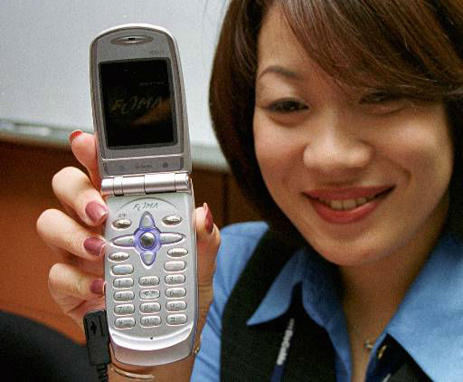 "<div class=""meta ""><span class=""caption-text "">NTT DoCoMo staff Yuko Matsumoto displays FOMA N2001 video-phone, a standard type handset of the world's first super-fast next-generation wireless service, at an office of Japan's top mobile carrier in Tokyo Wednesday, May 30, 2001 as the service for a limited 3,300 Japanese gadget fans, chosen from 147,000 applicants, began in the Tokyo area. The only models available were an upgraded, speedier version of NTT DoCoMo's current Net-linking i-mode phones while the most glamorous of the new phones, the video-phone, had been delayed for up to a month for software glitches. (AP Photo/Naokazu Oinuma) (AP Photo/ NAOKAZU OINUMA)</span></div>"