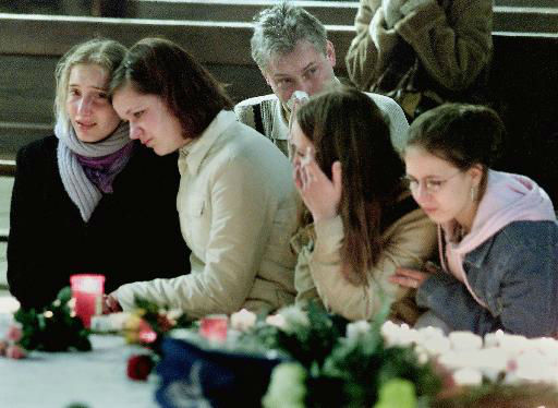 A man, background, and four young women mourn  the  victims of a school shooting in the Cathedral of Erfurt, eastern Germany,  Saturday,  April 27, 2002, the day after a former student of the Gutenberg school in Erfurt killed 16 people before he killed himself.  <span class=meta>(AP Photo&#47; MICHAEL PROBST)</span>