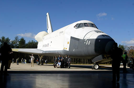 Workers pose in front of the Space Shuttle Enterprise prior to moving it into the new Steven F. Udvar-Hazy Center at Dulles Airport in Chantilly, Va., Thursday, Nov. 20, 2003. This is the last large artifact that will be moved before the offical opening of the museum annex on Dec. 15. &#40;AP Photo&#47;Lisa Nipp&#41; <span class=meta>(AP Photo&#47; LISA NIPP)</span>