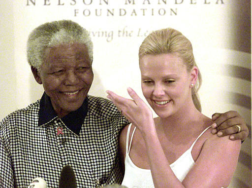 Former South African President Nelson Mandela, left, with South African-born best actress Oscar winner Charlize Theron, during a photo opportunity in Johannesburg Thursday March 11, 2004. Mandela hailed Theron for her hard work and success in Hollywood. &#40;AP Photo&#47;Denis Farrell&#41; <span class=meta>(AP Photo&#47; DENIS FARRELL)</span>
