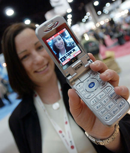 Melissa Elkins, with LG InfoComm U.S.A., takes video of herself using the company&#39;s new LG8000 cellular phone at Cellular Telecommunications and Internet Association convention Tuesday, March 23, 2004 in Atlanta. The phone, which is not on the market yet, shoots video as well as 1.3 mega-pixel still photos. &#40;AP Photo&#47;John Bazemore&#41; <span class=meta>(AP Photo&#47; JOHN BAZEMORE)</span>