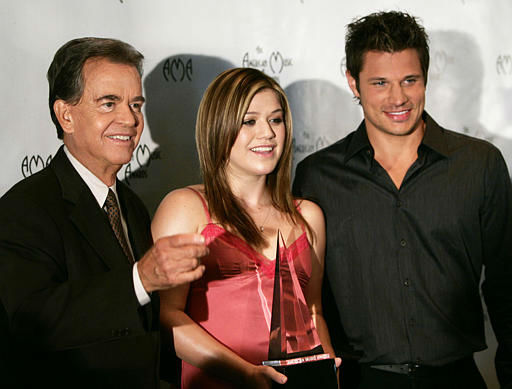 Producer Dick Clark, right, directs singer Kelly Clarkson, center, and Nick Lachey to photographers after they announced nominees for the annual American Music Awards, Tuesday, Sept. 14, 2004, in Beverly Hills, Calif. The awards are to be presented Nov. 14.  &#40;AP Photo&#47;Kevork Djansezian&#41; <span class=meta>(AP Photo&#47; KEVORK DJANSEZIAN)</span>