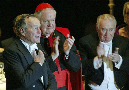 Former President George H.W. Bush, left, is applauded by Archbishop of New York Cardinal Edward Egan and former Governor of the State of New York Hugh L. Carey, right, after Bush spoke at the 59th annual Alfred E. Smith Memorial Foundation Dinner at the Waldorf Astoria hotel in New York, Thursday, Oct 21, 2004. &#40;AP Photo&#47;Stuart Ramson&#41; <span class=meta>(AP Photo&#47; STUART RAMSON)</span>