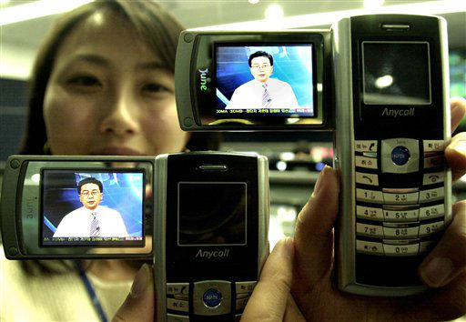 Ko Ji-hyun,  an employee of SK Telecom Broadcasting Technology Team, shows the world&#39;s first satellite digital multimedia broadcasting, DMB, phones, the SCH-B100 of Samsung Electronics, at the firm&#39;s office in Seoul, South Korea Monday, Jan. 10, 2005.  The world&#39;s first cell phone based-mobile broadcast Monday in South Korea with three video and six audio channels. Customers of SK Telecom., the country&#39;s largest mobile operator, can access the television service after purchasing SCH-B100 mobile phone that features a 2.2 inch liquid-crystal display and a battery capable of providing more than toe hours of viewing time. The model is priced at 1 million won &#40;US&#36;953&#41;.  &#40;AP Photo&#47;Ahn Young-joon&#41; <span class=meta>(AP Photo&#47; AHN YOUNG-JOON)</span>