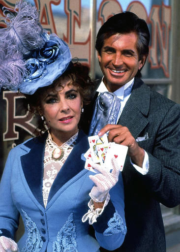 British actress Elizabeth Taylor stars as &#34;Alice Moffit&#34;, a displaced New Orleans gambler, in a TV Western drama. Taylor is pictured here in character, with George Hamilton who stars as her cousin. Exact date and location unknown. 1987. &#40;AP Photo&#47;CBS&#47;HO&#41; <span class=meta>(AP Photo&#47; XKR)</span>
