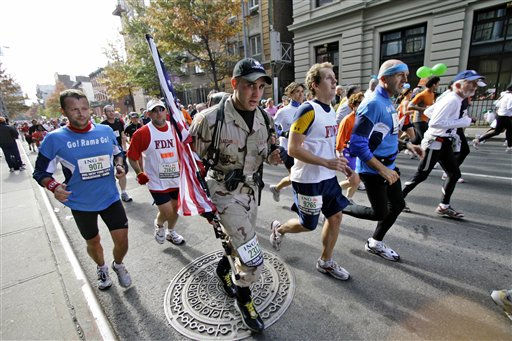 A participant carrying a United States flag and wearing a soldier&#39;s uniform runs through the Brooklyn borough of New York during the New York City Marathon in  Sunday, Nov. 5, 2006. Over 35,000 participants took part in the 26.2-mile marathon course passes through all five boroughs of New York.  &#40;AP Photo&#47;Mary Altaffer&#41; <span class=meta>(AP Photo&#47; MARY ALTAFFER)</span>