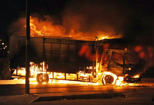 In this photo taken Sunday Feb. 27, 2011 a truck burns in Sohar, Oman. Protesters set a supermarket ablaze and gathered in several sites in a seaside town in Oman on Monday in a third consecutive day of unrest that has included deadly clashes in the strategic Gulf nation. Security forces sealed off main roads to Sohar, about 120 miles &#40;200 kilometers&#41; northwest of the capital of Muscat, in attempts to isolate the protesters and keep crowds from swelling.  &#40;AP Photo&#41; <span class=meta>(AP Photo&#47; STR)</span>