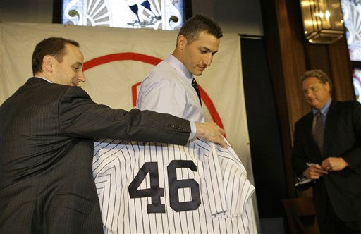 New York Yankees general manager Brian Cashman, left, helps left-handed pitcher Andy Pettitte, 34,  don his jersey as Yankees president Randy Levine, right, looks on during a news conference welcoming Pettitte back to the team he pitched for from 1995-2003 at Yankee Stadium in New York, Thursday, Jan. 11, 2007.  Pettitte, who turned down a &#36;12 million offer to stay with the Houston Astros, signed a one-year contract with the Yankees for &#36;16 million. &#40;AP Photo&#47;Kathy Willens&#41; <span class=meta>(AP Photo&#47; Kathy Willens)</span>
