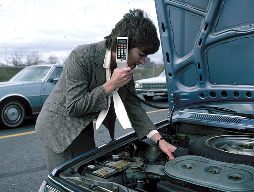 In this staged photo from General Electric, a stranded motorist calls a service station from an in-car cellular phone, 1983.  Mobile telephone service is now available in the Chicago area and soon to be available in Seattle, Phoenix, Denver, Minneapolis-St. Paul and Los Angeles as well as Canadian cities Toronto and Montreal.  The phones, like this one by GE, cost about &#36;2,500 installed.  &#40;AP Photo&#47;General Electric&#41; <span class=meta>(AP Photo&#47; Anonymous)</span>