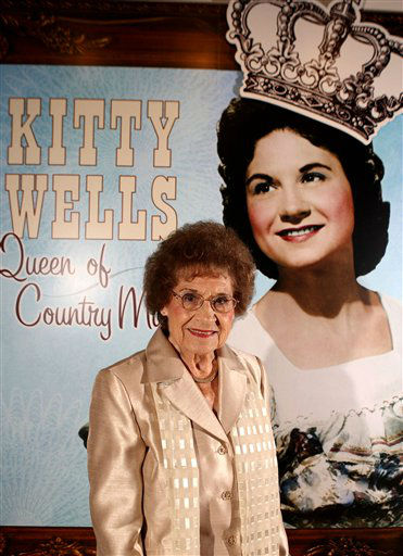 FILE - This Aug. 14, 2008 file photo originally released by the Country Music Hall of Fame and Museum shows music pioneer Kitty Wells at an exhibit honoring her career in Nashville, Tenn.  Wells, the first female superstar of country music, has died at the age of 92. The singer?s family says Wells died at her home Monday after complications from a stroke. Her recording of &#34;It Wasn&#39;t God Who Made Honky Tonk Angels&#34; in 1952 was the first No. 1 hit by a woman soloist on the country music charts. Other hits included &#34;Making Believe&#34; and a version of &#34;I Can&#39;t Stop Loving You.&#34;  &#40;AP Photo&#47;Country Music Hall of Fame and Museum, Donn Jones, file&#41; <span class=meta>(AP Photo&#47; Donn Jones)</span>