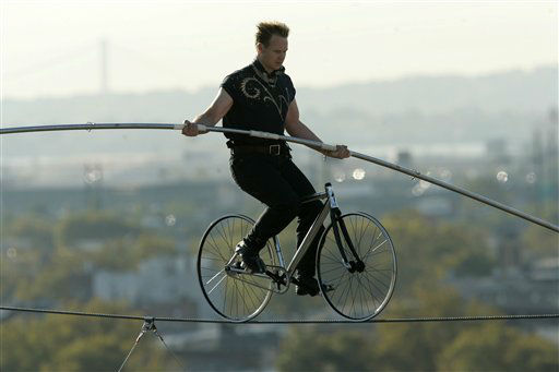 Nik Wallenda, a circus high-wire daredevil and the seventh generation of the Flying Wallendas circus family,  pedals a bicycle on a wire 12 stories above the street in Newark, N.J., Wednesday, Oct. 15, 2008. Wallenda was trying for a Guinness World Record for the longest distance and greatest height ever traveled by a bike on a high wire.  &#40;AP Photo&#47;Mike Derer&#41; <span class=meta>(AP Photo&#47; Mike Derer)</span>