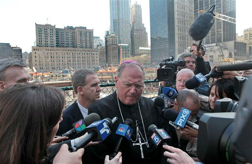 "<div class=""meta image-caption""><div class=""origin-logo origin-image ""><span></span></div><span class=""caption-text"">Archbishop Timothy Dolan listens as he is surrounded by reporters during his first visit to the World Trade Center site in  New York, Friday, April 24, 2009. Dolan knelt in prayer at ground zero and says he felt ""overwhelming sadness"" at the site of the worst terrorist attack in the nation's history. (AP Photo/Bebeto Matthews) (AP Photo/ Bebeto Matthews)</span></div>"