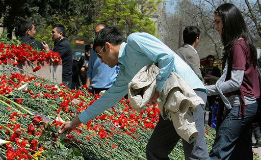 People lay flowers at the site of Thursday&#39;s stunning shooting in Baku&#39;s Oil Academy, Friday, May 1, 2009. A young man armed with an autoamtic pistol and clips of ammunition rampaged through a pretigious institute in the Azerbaijani capital Thursday, killing 12 people and wounding others before killing himself as police closed in, the government said. Little is known about the gunman and even less about the motive for the bloodshed that shook the faculty and students of the Azerbaijan State Oil Academy, a noted school whose graduates have included future presidents and tycoons.&#40;AP Photo&#47;Aydin Mamedov&#41; <span class=meta>(AP Photo&#47; Aydin Mamedov)</span>