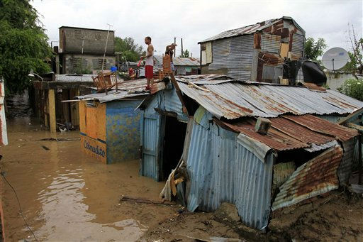 "<div class=""meta ""><span class=""caption-text "">A resident of the flooded Madre Vieja neighborhood in San Cristobal, Dominican Republic stands on the roof of his house after the passing of Hurricane Irene on Wednesday, Aug. 24, 2010. Flooding, rising rivers and mudslides have prompted the Dominican Republic government to evacuate nearly 38,000 people and more slides were likely in coming days because of days of intense rain from the storm system. (AP Photo/Roberto Guzman) (AP Photo/ Roberto Guzman)</span></div>"