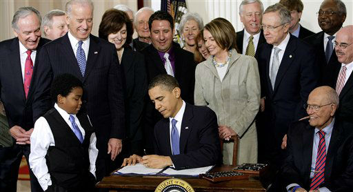 FILE - In this March 23, 2010 file photo President Barack Obama signs the health care bill in the East Room of the White House in Washington. He is flanked by Marcelas Owens of Seattle, left, and Rep. John Dingell, D-Mich. Behind, from left are, Sen. Tom Harkin, D-Iowa., Senate Majority Whip Richard Durbin of Ill., Vice President Joe Biden, Vicki Kennedy, widow of Sen. Ted Kennedy, Sen. Christopher Dodd, D-Conn., Rep. Sander Levin, D-Mich., Ryan Smith of Turlock, Calif., Health and Human Services Secretary Kathleen Sebelius, House Speaker Nancy Pelosi of Calif., House Majority Leader Steny Hoyer of Md., Senate Majority Leader Harry Reid of Nev., Rep. Patrick Kennedy, D-R.I., House Majority Whip James Clyburn of S.C., and Rep. Henry Waxman, D-Calif. The Supreme Court said Monday it will hear arguments in March over President Barack Obama?s health care overhaul, setting up an election-year showdown over the White House&#39;s main domestic policy achievement. &#40;AP Photo&#47;J. Scott Applewhite, File&#41; <span class=meta>(AP Photo&#47; J. Scott Applewhite)</span>