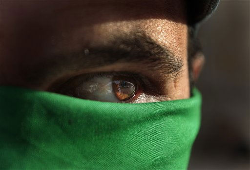 A pro Gadhafi supporter wears a green scarf on his face in Tripoli, Libya, Tuesday March 29, 2011. Libyan government tanks and rockets pounded rebel forces into a panicked full retreat Tuesday after an hours long, back-and-forth battle that highlighted the superior might of Col. Moammar Gadhafi&#39;s  forces, even hobbled by international airstrikes.&#40;AP Photo&#47;Jerome Delay&#41; <span class=meta>(AP Photo&#47; Jerome Delay)</span>