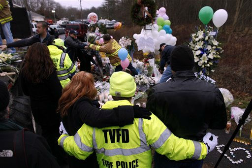 Onlookers embrace as firefighters and other volunteers reorganize a memorial for shooting victims near Sandy Hook Elementary School before erecting a shelter over it, Sunday, Dec. 16, 2012 in Newtown, Conn.  A gunman walked into Sandy Hook Elementary School in Newtown on Friday and opened fire, killing 26 people, including 20 children. &#40;AP Photo&#47;Jason DeCrow&#41; <span class=meta>(AP Photo&#47; Jason DeCrow)</span>