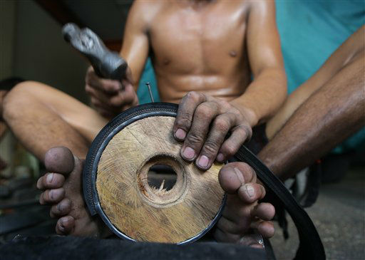 A Filipino man uses his feet to hold a wooden wheel to fasten strips of used rubber tires at a shop selling pushcart wheels made from used materials in Manila, Philippines on Monday July 8, 2013. The wheel sets made from used wheel bearings, old rubber tires, used tin cans and steel rods are sold from P500 to P1,600 &#40;US &#36;11 to &#36;37&#41; per set of three. &#40;AP Photo&#47;Aaron Favila&#41; <span class=meta>(AP Photo&#47; Aaron Favila)</span>