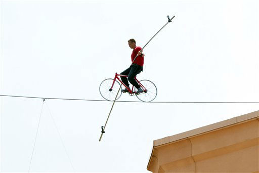 Nik Wallenda, a seventh-generation high-wire daredevil, pedals a bicycle across the Bridge Suite of the Paradise Island Atlantis resort in Nassau, Bahamas, Saturday, Aug. 28, 2010. Wallenda, of the famous Flying Wallendas circus family, cycled safely more than 100 feet &#40;31 meters&#41; along the wire some 260 feet &#40;79 meters&#41; above the turquoise ocean without a safety net to break his own Guinness World Record set in 2008 in Newark, New Jersey. &#40;AP Photo&#47;Craig Lenihan&#41; <span class=meta>(AP Photo&#47; Craig Lenihan)</span>