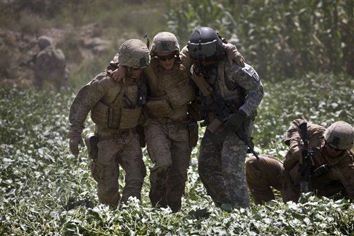 In this Sept. 2, 2010 photo, a U.S. Marine, left, and U.S. Amy Flight Medic Staff Sgt. Richard Jarrett, right, rush U.S. Marine Pfc. Justin Turner, center, of Flower Mound, Texas, who was wounded in an IED attack, across an irrigated field deep with mud to a waiting U.S. Army Task Force Shadow medevac helicopter, west of Lashkar Gah, in southern Afghanistan. Aeromedical teams with the 101st Airborne&#39;s Task Force Destiny provide the fast medical evacuation of those wounded throughout southern Afghanistan. &#40;AP Photo&#47;Brennan Linsley&#41; <span class=meta>(AP Photo&#47; Brennan Linsley)</span>