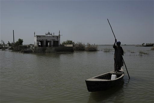 A Pakistani man who survived floods uses a boat in a flooded area in Sujawal, Sindh Province, southern Pakistan, Saturday, Sept. 25, 2010. Monsoon rains triggered massive floods six weeks ago that spread across the country and are still continuing in parts of the south. Some 8 million people have been made homeless in what Pakistani and U.N. officials have said is one of the largest humanitarian disasters in living memory. &#40;AP Photo&#47;Vincent Yu&#41; <span class=meta>(AP Photo&#47; Vincent Yu)</span>