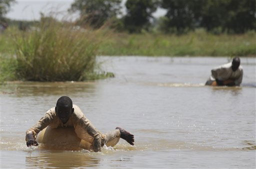 Local residents use calabash gourds as flotation devices as they swim across flooded farmland in Gudinchin village, near Dutse in northern Nigeria, Monday, Sept. 27, 2010. Farmers in northern Nigeria said Monday they feared their crops were destroyed in weekend floods that started when two swollen dams overflowed and displaced 2 million people. In the village of Gudinchin, rice and corn stalks poked above a fast-moving river that had washed over the fields. A few houses in the village peered above the water, and people had constructed a makeshift embankment out of the remains of mud houses that had washed away. &#40;AP Photo&#47;Sunday Alamba&#41; <span class=meta>(AP Photo&#47; Sunday Alamba)</span>