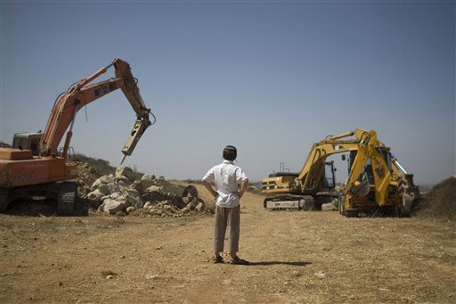 A Jewish settler boy looks at earth-moving equipment working at a construction site in the West Bank Jewish settlement of Ariel, Monday, Sept. 27, 2010. Senior Palestinian official Yasser Abed Rabbo said Monday that President Mahmoud Abbas remains ready to walk out on Mideast peace talks if Israel resumes construction in its West Bank settlements now that building restrictions have expired.  <span class=meta>(AP Photo&#47; Ariel Schalit)</span>