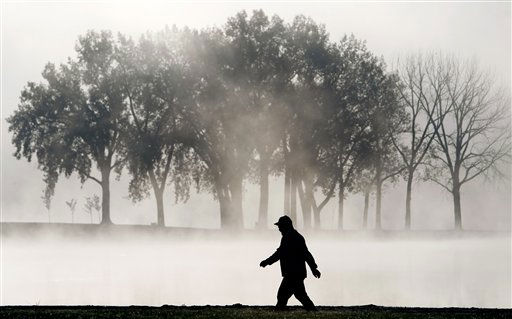 A man walks on a path as fog rises over the lake at Gray&#39;s Lake Park in Des Moines, Iowa on Monday, Sept. 27, 2010.  <span class=meta>(AP Photo&#47; Charlie Neibergall)</span>