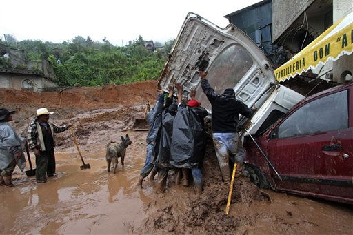 "<div class=""meta ""><span class=""caption-text "">Men inspect a vehicle buried under mud after a landslide in the town of Santa Maria de Tlahuitoltepec, Mexico Tuesday Sept. 28, 2010. A mudslide first thought to have buried hundreds of people has left 11 missing and there are no confirmed dead, authorities said, backing off earlier predictions of a catastrophe in Mexico's rain-soaked southern state of Oaxaca. (AP Photo/ Luis Alberto Cruz Hernandez)</span></div>"