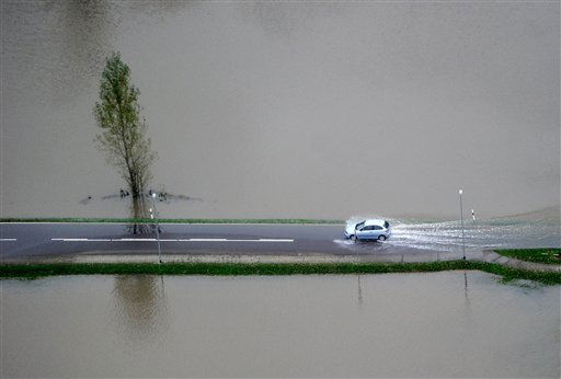 Aerial view of a car driving on a partially flooded road in Kleiunkugel in eastern Germany, on Tuesday, Sept. 28, 2010. Heavy rainfalls overnight caused flooding in the area near the Polish border.  <span class=meta>(AP Photo&#47; Oliver Lang)</span>