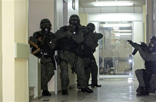 Soldiers enter the police hospital where Ecuador&#39;s President Rafael Correa is being holed up by protesting police in Quito, Ecuador, Thursday Sept. 30, 2010.  The army rescued Correa from the hospital where he had been trapped by rebellious police for more than 12 hours while he was being treated for tear-gas fired by hundreds of police angry over a law that they claim would cut their benefits. &#40;AP Photo&#47;Dolores Ochoa&#41; <span class=meta>(AP Photo&#47; Dolores Ochoa)</span>