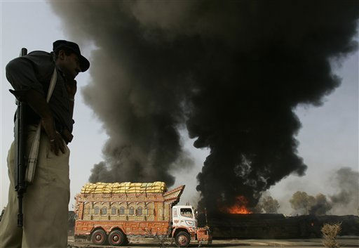 Pakistani police officer stands guard on still smoldering oil trucks in Shikarpur, southern Pakistan on Friday Oct. 1, 2010. Suspected militants set ablaze at least 27 tankers carrying fuel for U.S. and NATO troops in Afghanistan on Friday, police said. &#40;AP Photo&#47;Aaron Favila&#41; <span class=meta>(AP Photo&#47; Aaron Favila)</span>