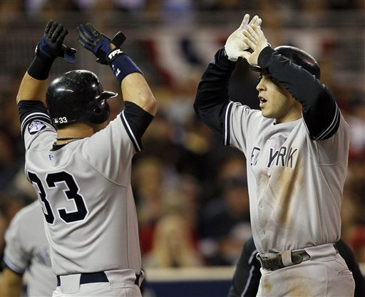 New York Yankees&#39; Nick Swisher &#40;33&#41; congratulates Mark Teixeira after Teixeira hit a two-run home run during the seventh inning of Game 1 of baseball&#39;s American League Division Series against the Minnesota Twins on Wednesday, Oct. 6, 2010, in Minneapolis. &#40;AP Photo&#47;Charlie Neibergall&#41; <span class=meta>(AP Photo&#47; Charlie Neibergall)</span>