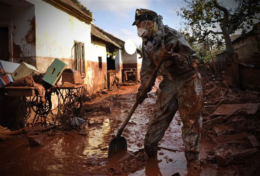 "<div class=""meta image-caption""><div class=""origin-logo origin-image ""><span></span></div><span class=""caption-text"">A Hungarian soldier, wearing protective gear, cleans a yard flooded by toxic mud in Devecser, Hungary, Thursday, Oct. 7, 2010. The toxic red sludge that inundated three Hungarian villages reached Europe's mighty Danube River on Thursday but no immediate damage was evident, Hungary's rescue operations agency said. The European Union and environmental officials had feared an environmental catastrophe affecting half a dozen nations if the red sludge, a waste product of making aluminum, contaminated Europe's second-longest river after bursting out of a factory's reservoir. (AP Photo/Bela Szandelszky) (AP Photo/ Bela Szandelszky)</span></div>"