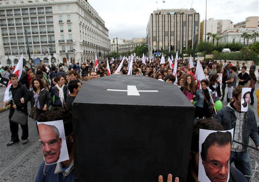 Protesters covering their faces with photos of Greek Premier George Papandreou, left, and Greek Finance Minister George Papaconstantinou, right, carry a symbolic coffin during a protest in Athens, Thursday, Oct. 7, 2010. Greece&#39;s state sector shut down Thursday as civil servants walked off the job in a 24-hour strike, demanding the government take back stringent austerity measures designed to pull the country out of a debt crisis. &#40;AP Photo&#47;Thanassis Stavrakis&#41; <span class=meta>(AP Photo&#47; Thanassis Stavrakis)</span>