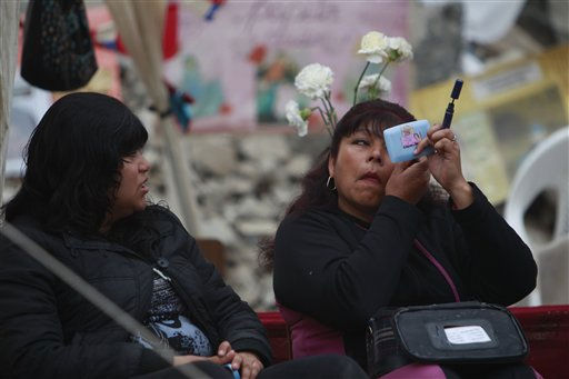 "<div class=""meta ""><span class=""caption-text "">A woman applies make-up while another watches a the camp where relatives wait for the rescue of trapped miners outside the San Jose mine, Copiapo, Chile, Friday, Oct. 8, 2010. Chile's mining minister says that just 130 feet, some 39 meters, remain before a drill breaks through to reach the chamber in the collapsed gold and copper mine where 33 trapped miners have waited more than two months to be rescued. (AP Photo/Natacha Pisarenko) (AP Photo/ Natacha Pisarenko)</span></div>"