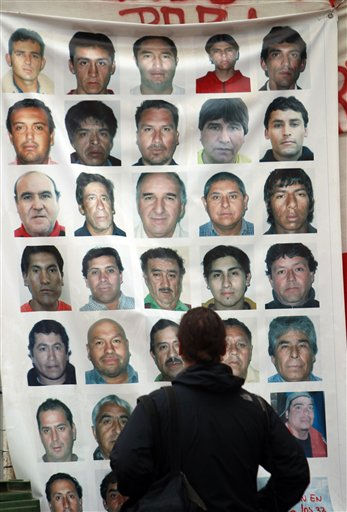 "<div class=""meta ""><span class=""caption-text "">A journalist looks at a banner with images of the 33 trapped miners at the San Jose Mine, Copiapo, Chile Friday, Oct. 8, 2010. Chile's mining minister says that just 130 feet, some 39 meters, remain before a drill breaks through to reach the chamber in the collapsed gold and copper mine where 33 trapped miners have waited more than two months to be rescued. (AP Photo/Natacha Pisarenko) (AP Photo/ Natacha Pisarenko)</span></div>"