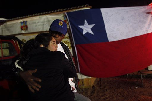 Ezequiel Rivera hugs his daughter at the camp were relatives of a trapped miners wait for news of the rescue effort as a Chilean flag hangs near the San Jose mine in Copiapo, Chile, Friday Oct. 8, 2010. Drillers neared the lower reaches of a gold and copper mine where 33 men have been trapped for more than two months, preparing Friday for a breakthrough. The mine collapsed on Aug. 5. &#40;AP Photo&#47;Natacha Pisarenko&#41; <span class=meta>(AP Photo&#47; Natacha Pisarenko)</span>